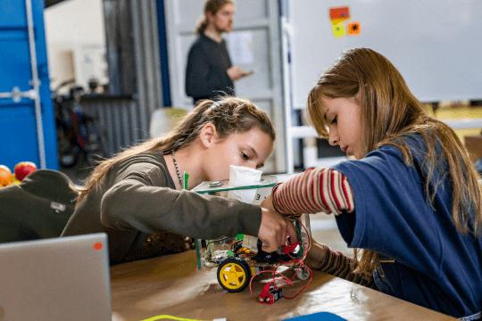 Jugendliche bauen gemeinsam an einem Roboter